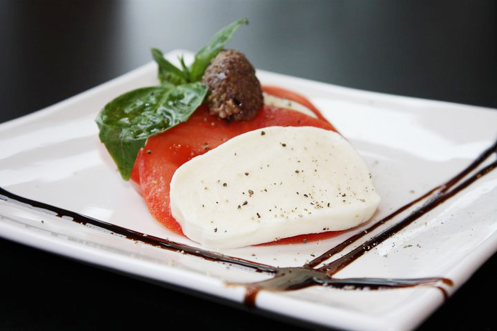 Fresh Mozarella and Vine Ripened Tomatoes with Three Olive Tapanade, drizzled with balsamic glaze